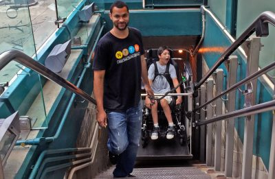 Transit Museum staff member operating the Museum's wheelchair lift for young transit fan.
