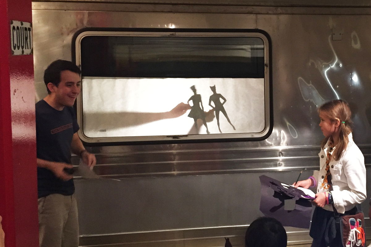 An educator and young transit fan create shadow puppets in the subway.