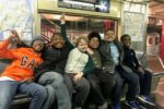 Six boys sitting and smiling together on a subway car.