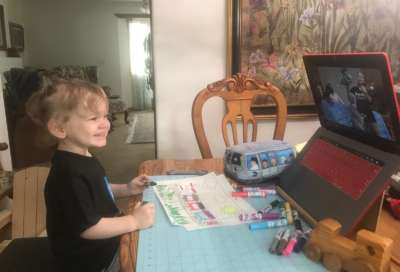 Child makes art at a table at home and smiles at a Museum educator on a computer screen.