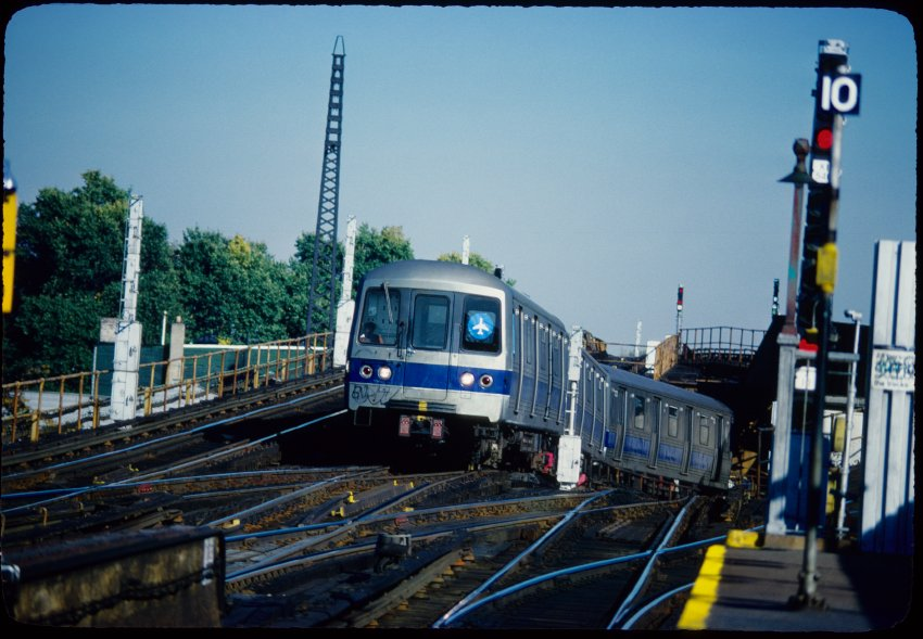color image of the JFK Express emerging outdoors after leaving a tunnel