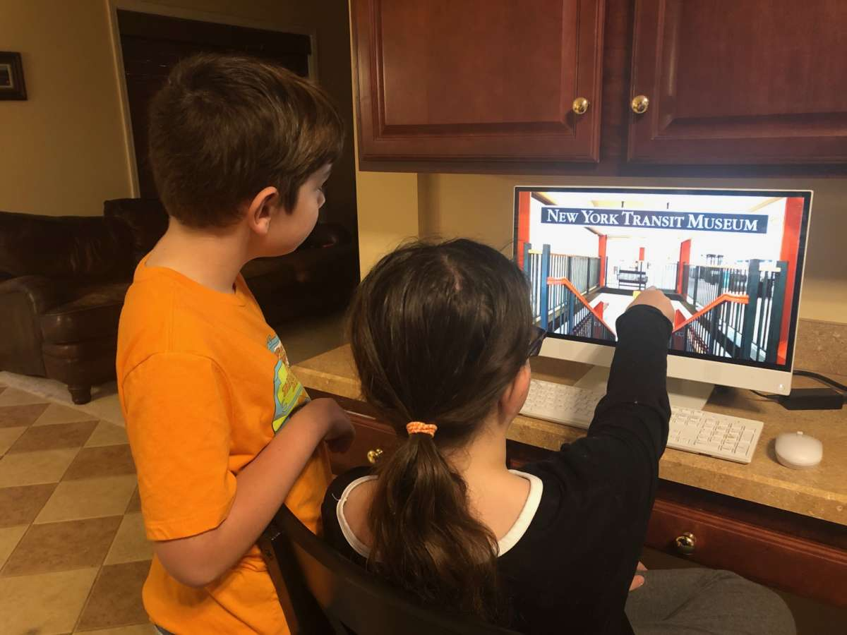 A boy and girl look at a computer screen showing the New York Transit Museum logo and a photo of inside the Museum.