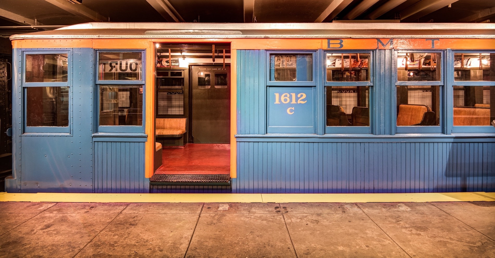 BMT World's Fair Car 1612C on view at the New York Transit Museum in Downtown Brooklyn. The train car is wooden and painted in a blue and orange color scheme.
